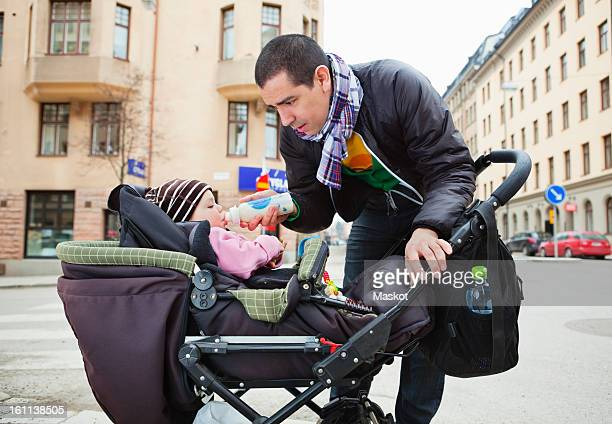 father feeding daughter (0-11 months) on street - 0 11 monate stock-fotos und bilder
