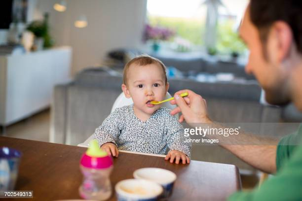 Father feeding daughter