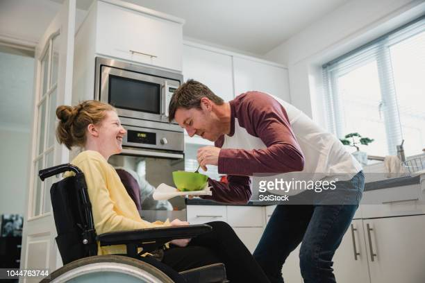 father feeding disabled daughter at home - epilepsy stock pictures, royalty-free photos & images