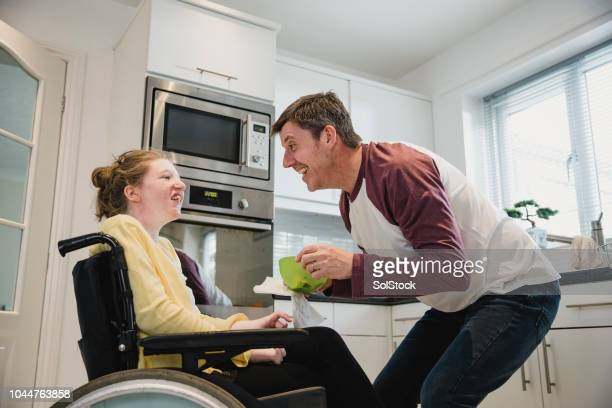 father feeding disabled daughter at home - als stock photos and pictures