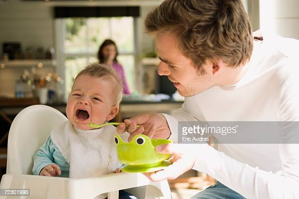 Father feeding her baby, crying