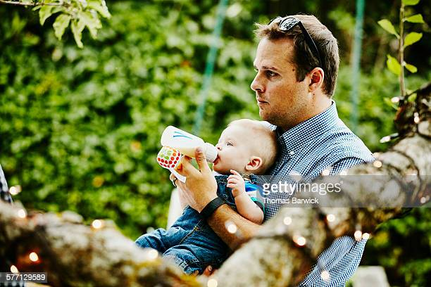 Father feeding infant son bottle during party