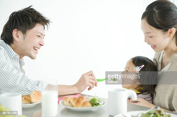 Father feeding meal to daughter, side view