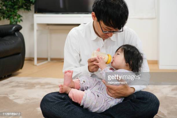 father feeding milk to baby at home - japanese breastfeeding stock pictures, royalty-free photos & images