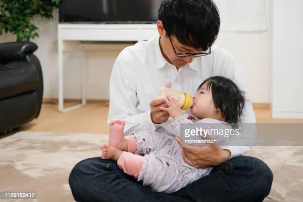 父は家で赤ちゃんにミルクを供給 - 主夫 ストックフォトと画像