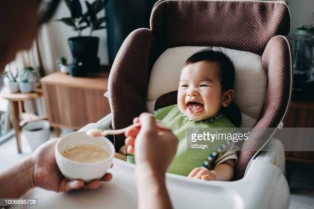 father feeding smiling happy baby solid food with spoon on high chair at home - pureed stock pictures, royalty-free photos & images
