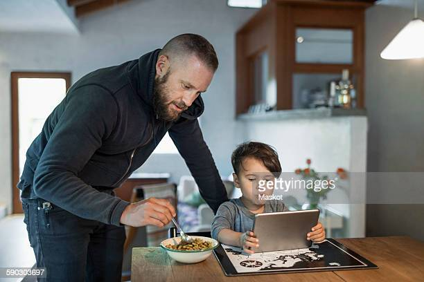 Father feeding son using digital tablet at table in house