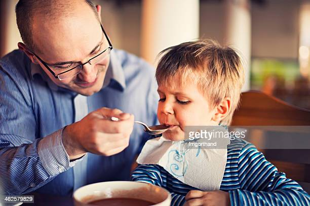 Father feeding son with soup