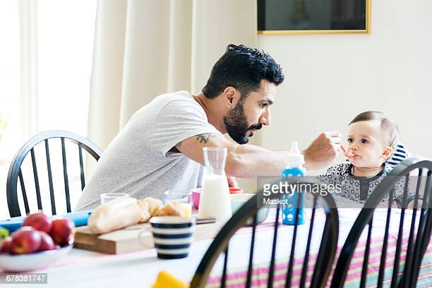 Father feeding toddler while sitting by girl during breakfast at home