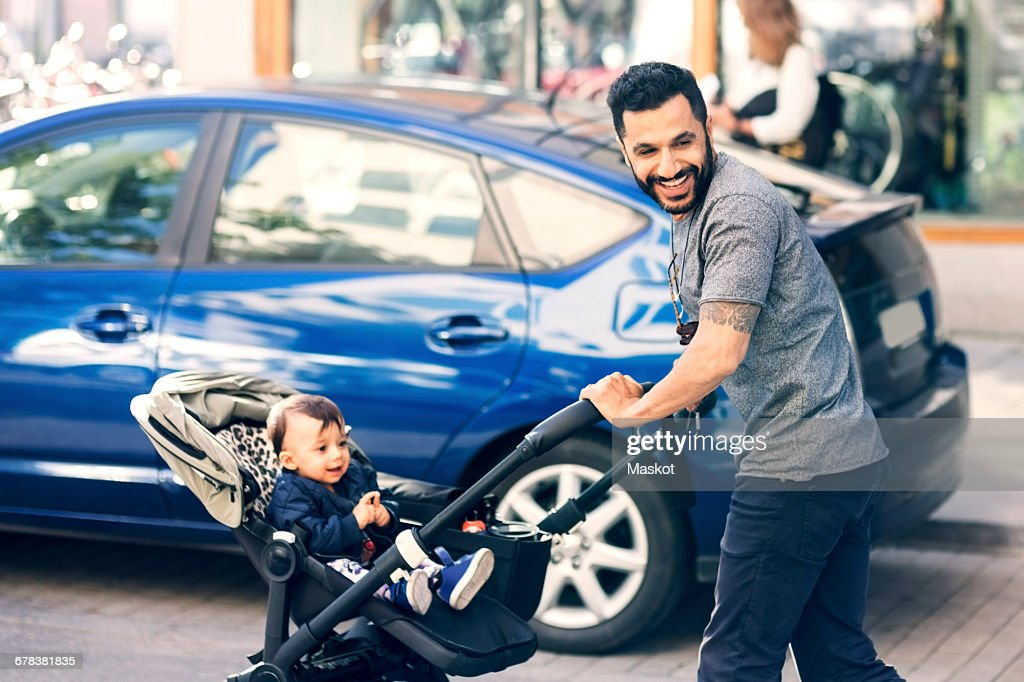 Father feeding toddler while standing by baby stroller on street : Stock Photo