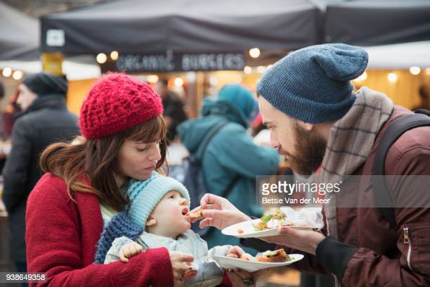 Father feeds baby boy while mother looks on, at street market.