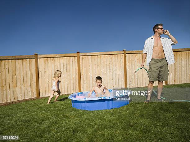 Father filling up a wading pool