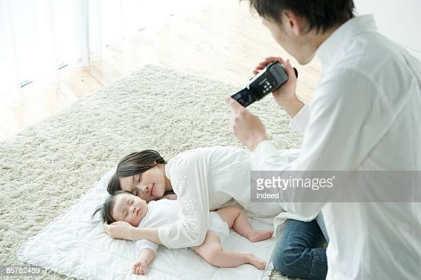 father filming sleeping mother and baby girl - adult video japan stock pictures, royalty-free photos & images