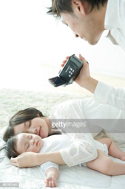 Father filming sleeping mother and baby girl