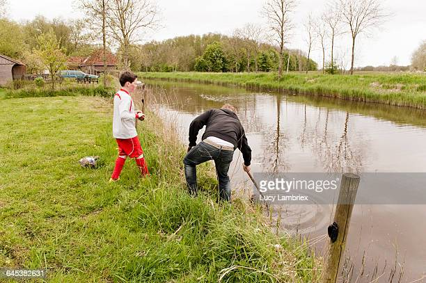 Father fishing soccer ball from ditch for son