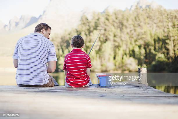 father fishing with son in lake - fishing tackle stock pictures, royalty-free photos & images
