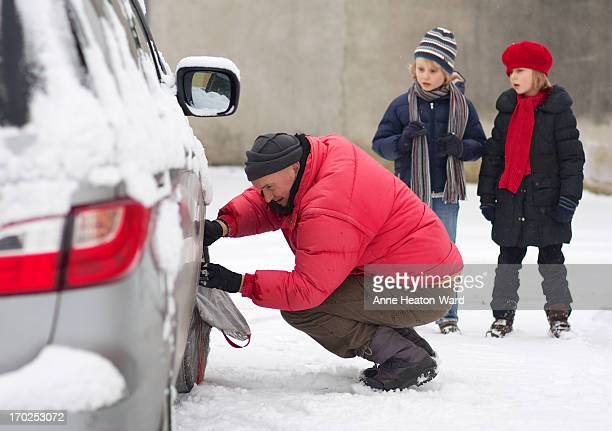 Father fitting a snow sock on family car