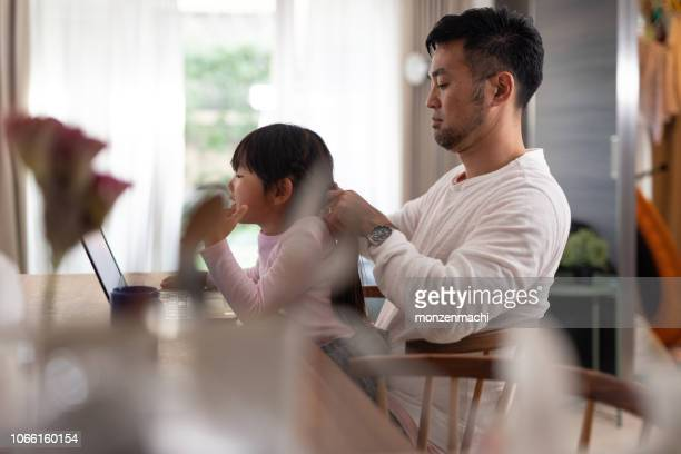 father fixing daughter's hair at home - braided hair stock pictures, royalty-free photos & images