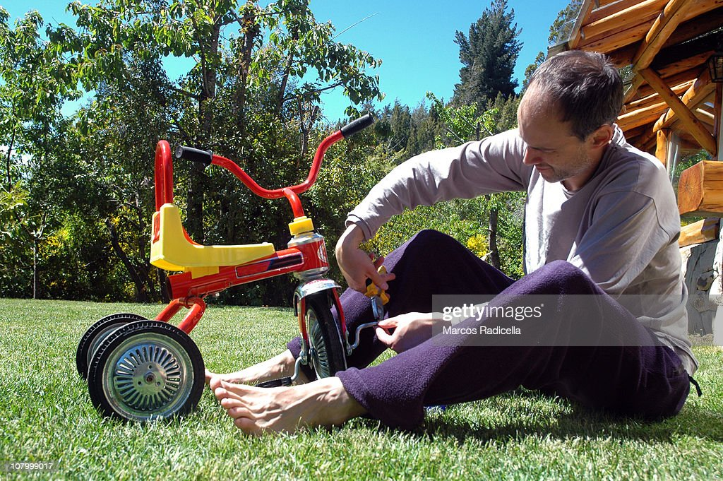 Father fixing tricycle : Stock Photo