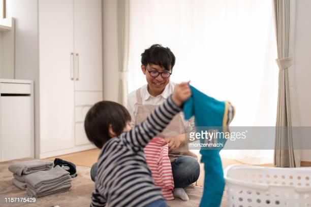 子供と洗濯物を折りたたむ父 - 主夫 ストックフォトと画像