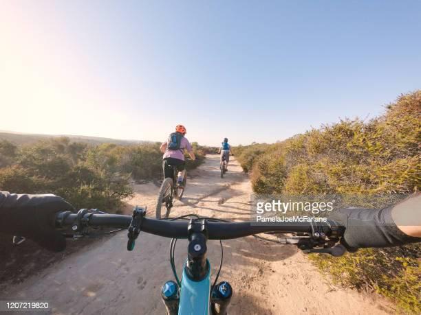 pov, padre che segue la famiglia in mountain bike lungo dirt trail - prospettiva del fotografo foto e immagini stock