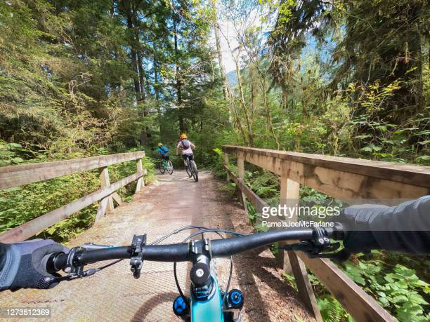 pov, father following family on mountain bikes while crossing bridge - vancouver canada stock pictures, royalty-free photos & images