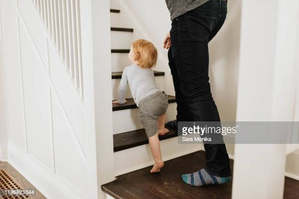 father following son crawling up stairway in house - unrecognisable person stock pictures, royalty-free photos & images