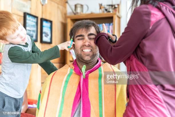 父は自宅の注文で滞在中に自宅で散髪を取得します - 髪を切る ストックフォトと画像