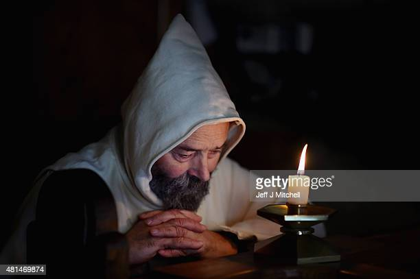 Father Giles Conacher lights a candle in the lady chapel at Pluscarden Abbey on July 21 2015 in Elgin Scotland Monks at Abbey which owes its...