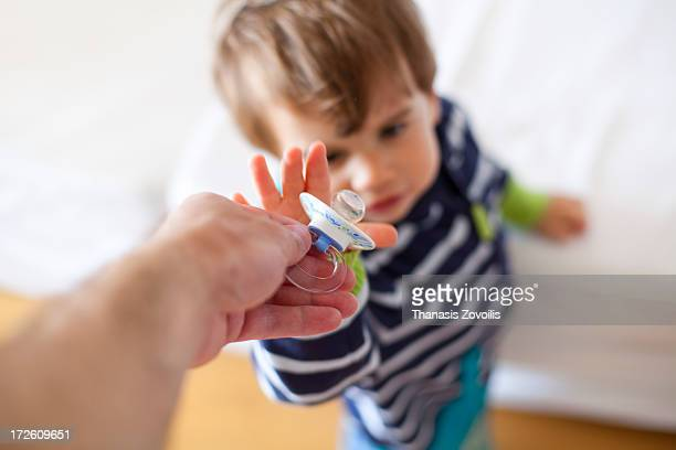Father give a pacifier to his son