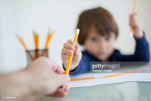 Father give a pencil to his kid