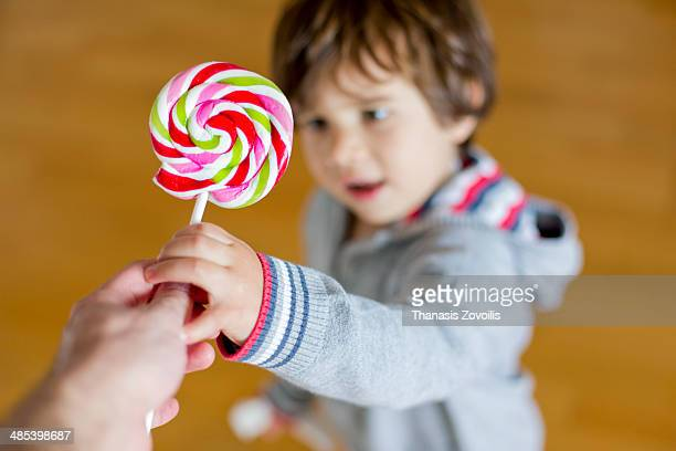 Father gives a lollipop to his kid