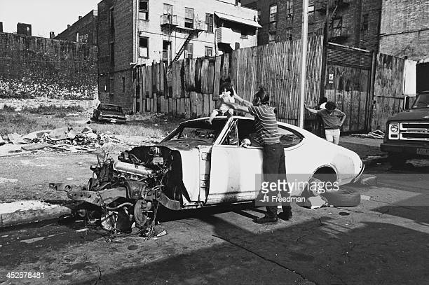 A father gives his daughter a sandwich on top of an abandoned car in the South Bronx New York City circa 1976