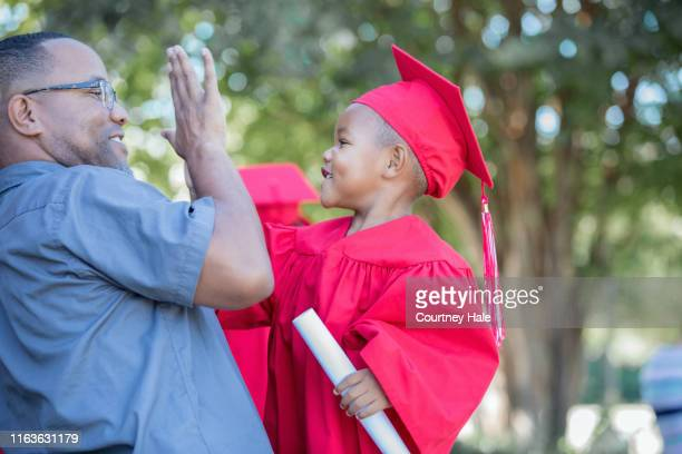 father gives his preschool age son a high five after kindergarten graduation ceremony - graduation clothing stock pictures, royalty-free photos & images