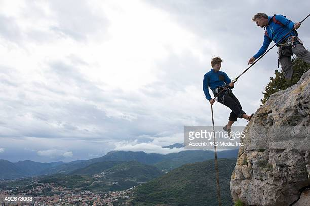 Father gives rappel advice to son, at cliff edge
