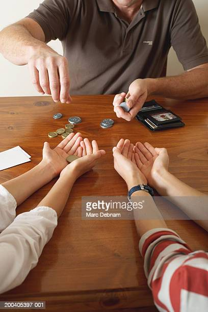 Father giving coins to children (10-12) across table, mid section, close-up