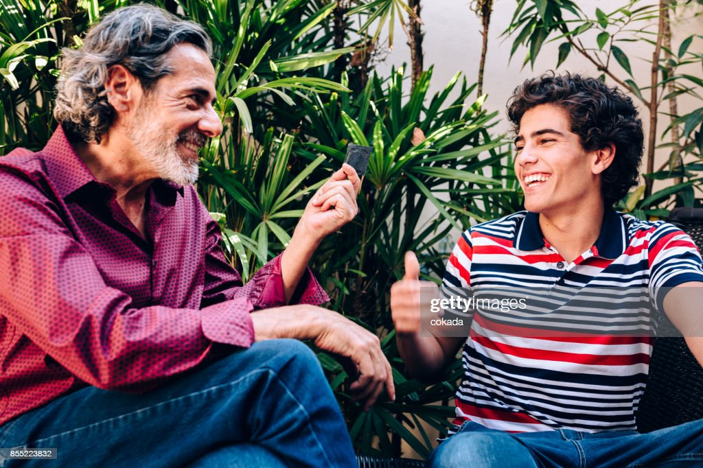 Father giving condom to his son : Stock Photo
