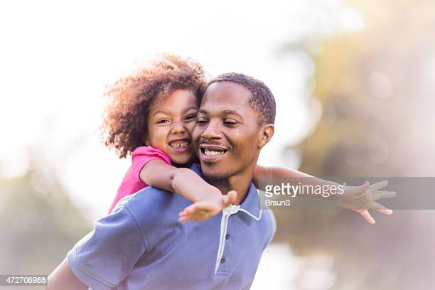Father giving daughter a piggyback ride on a sunny day