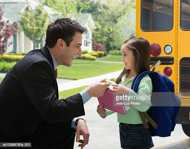 Father giving daughter (4-5) lunchbox for school