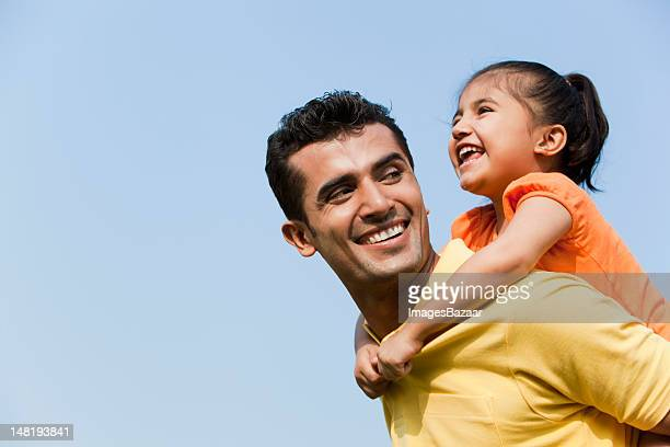 Father giving daughter (6-7) piggyback ride outdoors