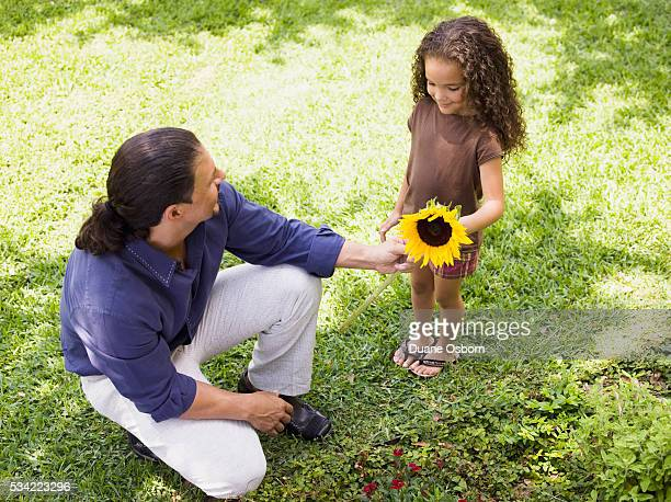 Father giving daughter sunflower from garden