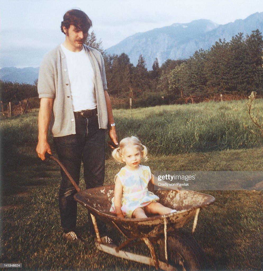 Father giving daughter wheelbarrow ride : Stock Photo
