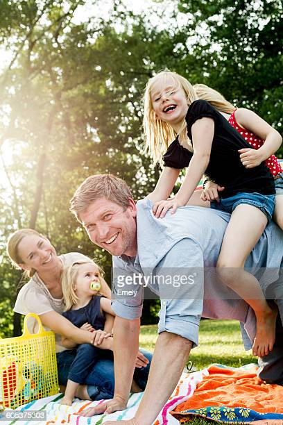 Father giving daughters piggyback at family picnic in park