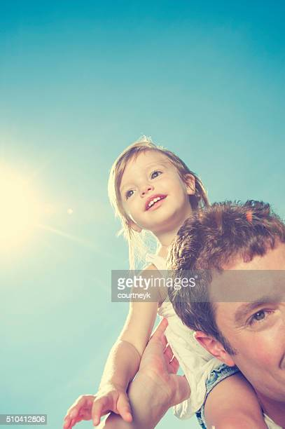 Father giving his daughter a piggy back ride.