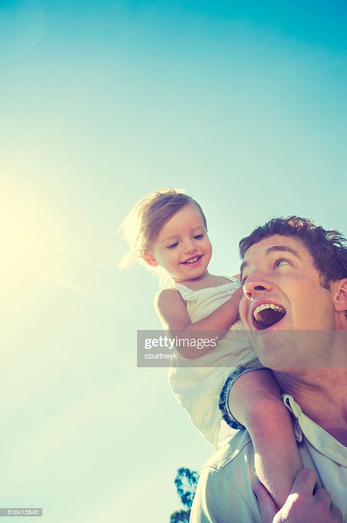 Father giving his daughter a piggy back ride. : Stock Photo