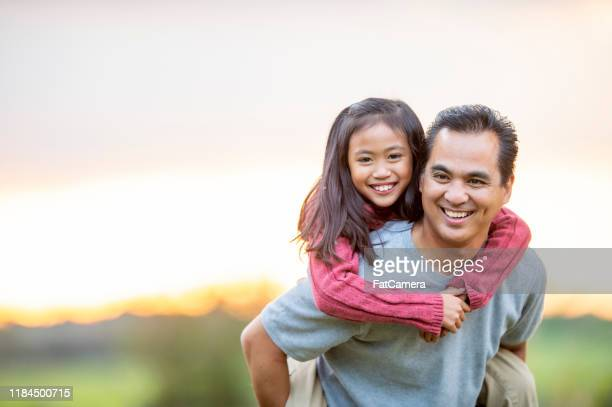 father giving his daughter a piggyback ride stock photo - filipino family stock pictures, royalty-free photos & images