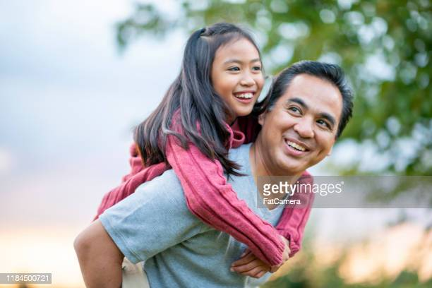 father giving his daughter a piggyback ride stock photo - iberian ethnicity stock pictures, royalty-free photos & images