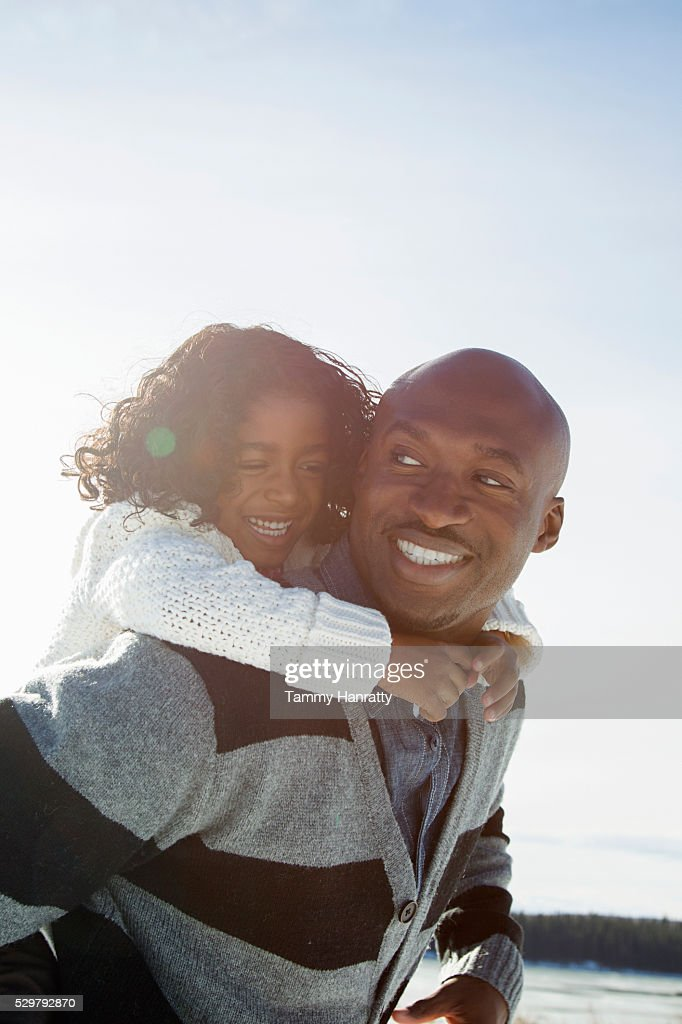 Father giving his daughter (10-12) piggy back ride : Stock Photo