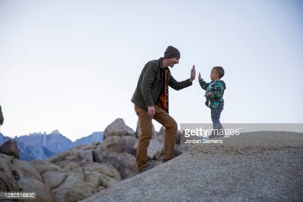 a father giving his son a high five on top of a rock. - rock stock pictures, royalty-free photos & images
