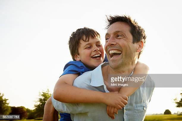 a father giving his son a piggyback. - cavalitas imagens e fotografias de stock